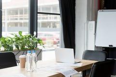 laptop, tapetuje i butelki woda na stole w nowożytnym biurze Zdjęcie Royalty Free