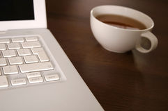 Laptop and tea cup Stock Image