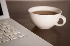 Laptop and tea cup Stock Photos