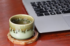 Laptop and tea cup. Laptop keyboard and tea cup Stock Photos