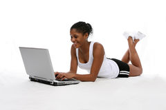 Laptop Teen. Pretty African American teenage girl in athletic clothes, on her stomach, working on a laptop while smiling Stock Photo