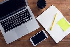 Laptop, telefon komórkowy, rozporządzalny szkło, pióro i organizator na drewnianym stole, zdjęcia royalty free