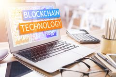 Blockchain concept. Laptop with text on screen placed on messy office desktop with supplies and other items. Blockchain concept Royalty Free Stock Photos