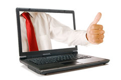 Laptop and thumb up. Hand with thumb up come out from a screen of a laptop computer, isolated on white background. Symbol of success and agreement Royalty Free Stock Photography