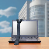 Laptop, tie in the office interior Royalty Free Stock Images