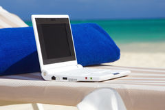Laptop and towel on the beach chaise longue. Laptop computer and towel on the beach chaise longue royalty free stock photography