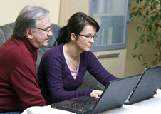 Laptop tutoring. A woman tutoring a senior man how to use a laptop Stock Image