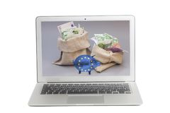 Laptop with Two money bag with euro and glass piggy bank with Flag of European Union on screen stock photo