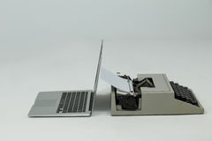 Laptop and typewriter on grey background Stock Images