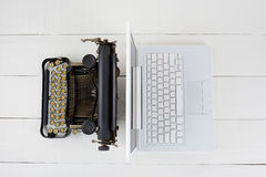 Laptop and Typewriter. Overhead shot of and old fashioned typewriter back-to-back with a modern laptop computer on a white wood desk Royalty Free Stock Photography