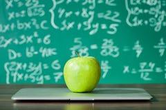 Laptop und Apfel auf dem Schreibtisch Lizenzfreies Stockfoto