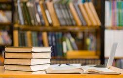 Laptop und ein Stapel Bücher in der Bibliothek Lizenzfreies Stockfoto