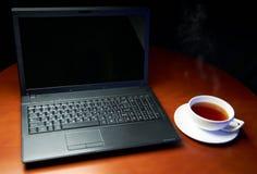 Laptop und eine Schutzkappe des Tees Lizenzfreies Stockbild