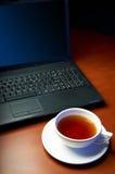 Laptop und eine Schutzkappe des Tees Stockfotos