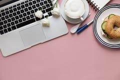 Laptop und Frühstück auf rosa Hintergrund Lizenzfreie Stockfotografie