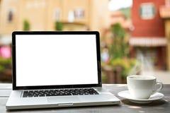 Laptop und Kaffeetasse auf hölzernem mit defocus der antiken Stadt Stockfotos