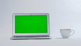 Laptop und Kaffeetasse auf weißem Hintergrund, grüner Schirm Stockbild