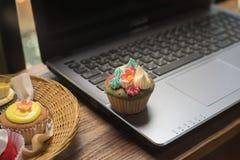 Laptop und kleine Kuchen Lizenzfreies Stockbild