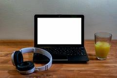 Laptop und Kopfhörer auf einem Holztisch Stockfoto