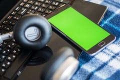 Laptop und Kopfhörer Smartphone mit grünem Schirm für Schlüssel-chrom stockfoto