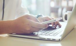 Laptop und Mobiltelefon auf einem weißen Hintergrund Stockbild