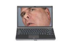 Laptop und neugieriger Mann Stockbild