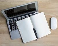 Laptop und Notizblock mit Stift - Draufsicht über Holztisch Lizenzfreies Stockfoto