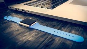 Laptop und smartwatch auf dem Tisch, grauer Aluminiumkörper Stockfoto