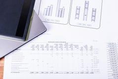 Laptop und Tablette sind auf den Dokumenten und den Zeitplänen Lizenzfreies Stockbild