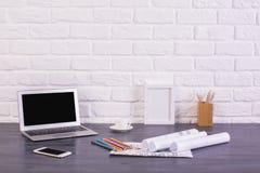 Laptop und Telefon auf Schreibtisch Lizenzfreies Stockbild