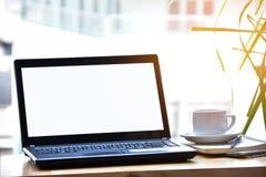 Laptop und weiße Kaffeetasse auf Holztisch am sonnigen Tag Stockbilder