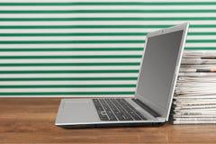 Laptop und Zeitungen Stockbilder