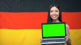 Laptop van de meisjesholding met het groene scherm, Duitse vlag op achtergrond, het reizen stock videobeelden