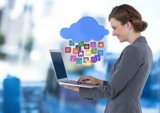 Laptop van de onderneemsterholding met wolken apps pictogrammen in blauwe motie openbare ruimte Stock Foto's