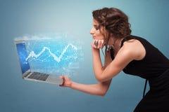 Laptop van de vrouwenholding met financieel concept stock fotografie