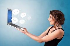 Laptop van de vrouwenholding met toespraakbellen royalty-vrije stock afbeeldingen