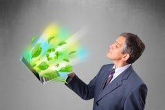 Laptop van de zakenmanholding met kringloop en milieusymbo stock afbeeldingen