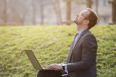 Laptop van de zakenmanholding in openlucht en vullende energie van sunr stock foto's