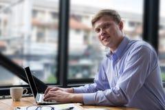 Laptop van het zakenmangebruik met het document van het businessplan op het werk stock fotografie