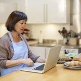 Laptop van huisvrouwensearching preparing menu Concept stock afbeeldingen