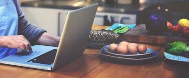 Laptop van huisvrouwenserching preparing menu Concept stock foto