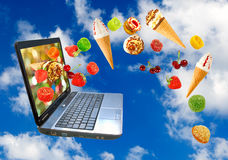 Laptop and various sweets on sky background royalty free stock photography