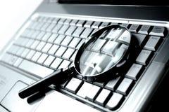 Laptop + Vergrootglas Stock Afbeeldingen