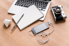 Laptop, vintage camera, mobile phone, earphones and notebook with pen Stock Images