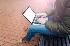 Laptop w mężczyzna ` s wręcza obsiadanie na drewnianym krześle w parku Ubierający w niebieskich dżinsach i dębników butach Mockup Fotografia Stock