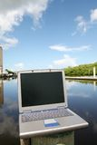 Laptop on the water. A photo of a laptop set on top of a dock post in the bay Stock Photo