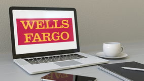 Laptop with Wells Fargo logo on the screen. Modern workplace conceptual editorial 3D rendering. Laptop with Wells Fargo logo on the screen. Modern workplace Stock Photo