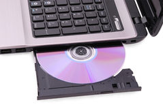 Laptop on white background. DVD disc in the drive Stock Photos