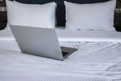 Laptop on white bed work at home stock photo