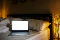 The laptop in the white bedroom. Lamps lightning softly. Stock Photo